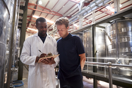 Two men working at a wine factory making notes, close up