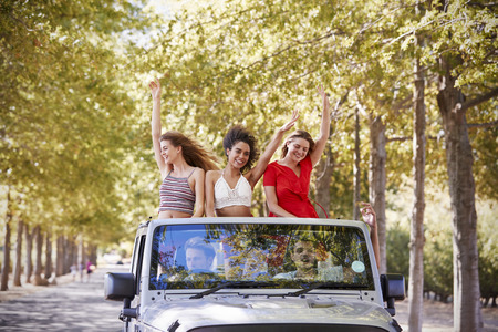 Girlfriends standing in the back of an open top car waving