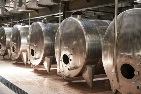 A row of metal vats in a modern winemaking facility