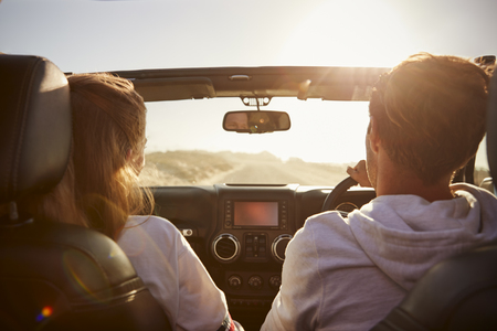 Couple driving look at each other, hold hands, passenger POV Stock Photo