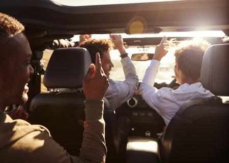 Three young adult men having fun driving an open top car Stock Photo