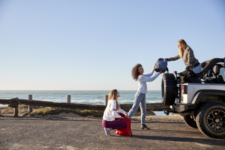 Three young adult girlfriends unloading backpacks from a car Stock Photo