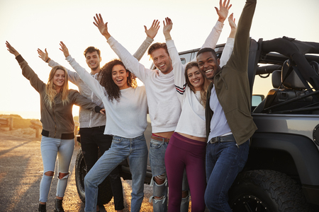 Young adult friends with hands in the air standing by their truck, close up Stok Fotoğraf