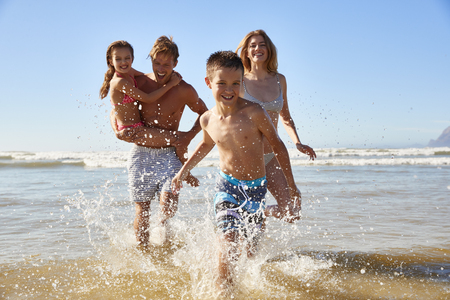 Family On Summer Beach Vacation Run Out Of Sea Towards Camera Standard-Bild
