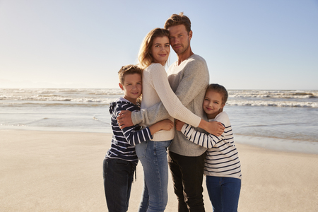 Portrait Of Loving Family Embracing On Winter Beach Stock Photo