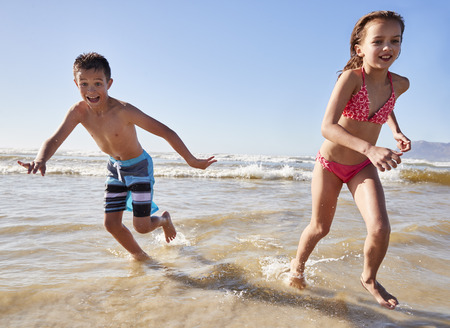 Boy And Girl On Summer Vacation Running Through Waves