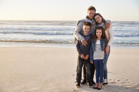 Portrait de famille marchant ensemble le long de la plage d'hiver