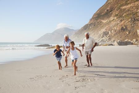 Grandparents Running Along Beach With Grandchildren On Summer Vacation Foto de archivo