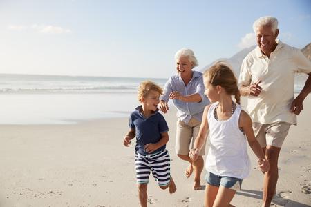 Großeltern laufen entlang Strand mit Enkelkindern auf Sommerferien