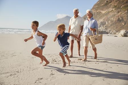 Grandparents Running Along Beach With Grandchildren Standard-Bild