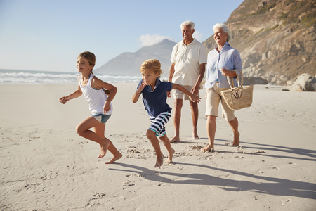 Grandparents Running Along Beach With Grandchildren Stockfoto