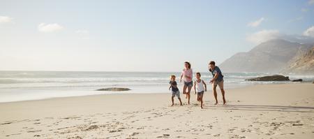 夏休みに子供たちと一緒にビーチで走る両親 写真素材