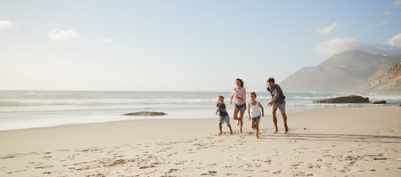 Parents Running Along Beach With Children On Summer Vacation