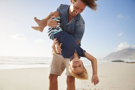 Father Having Fun With Son On Summer Beach Vacation Stock Photo