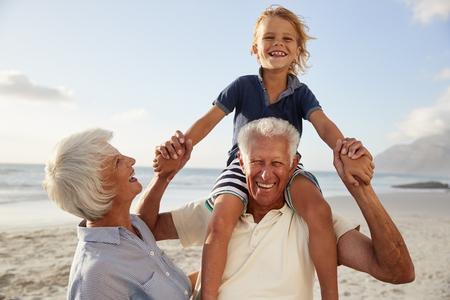 Großeltern , die Enkel auf Schultern auf Spaziergang entlang Strand tragen Standard-Bild - 99604381