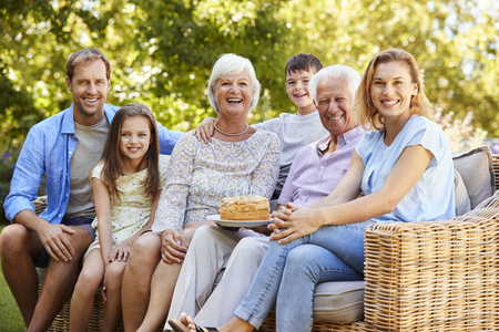 Three generation family sitting together in the garden Stock Photo