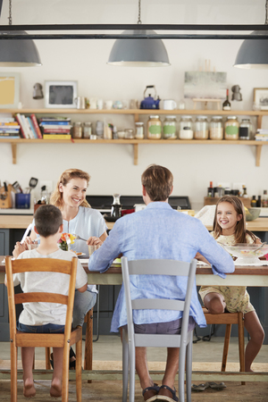 Family having lunch together in their kitchen, vertical