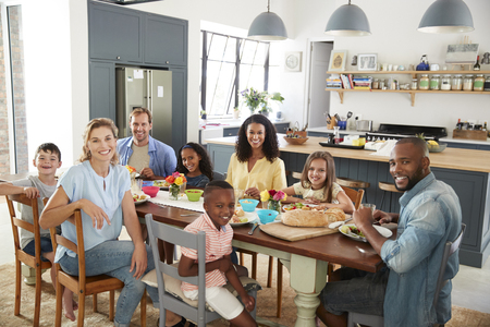 Two families having lunch together at home looking to camera Stock Photo