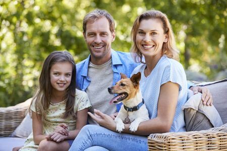 Parents and daughter sitting with their dog in the garden Stock Photo