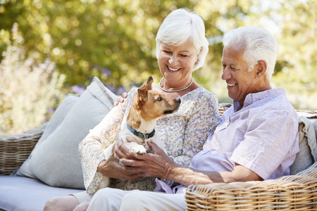 Happy senior couple sitting with a pet dog in the garden Stock fotó - 99606631