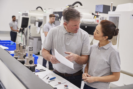 Engineer And Female Apprentice Discussing Job Sheet In Factory Stock Photo