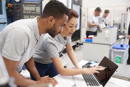 Two Engineers Using CAD Programming Software On Laptop Stock Photo