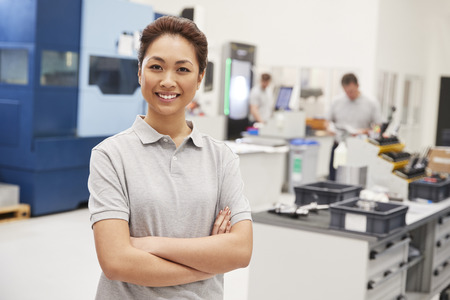 Portrait Of Female Engineer On Factory Floor Of Busy Workshop Stock Photo