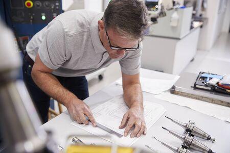Male Engineer Measuring CAD Drawings In Factory 免版税图像