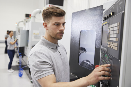 Male Engineer Operating CNC Machinery In Factory