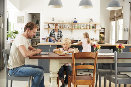 Busy family kitchen, dad and son working at table, close up