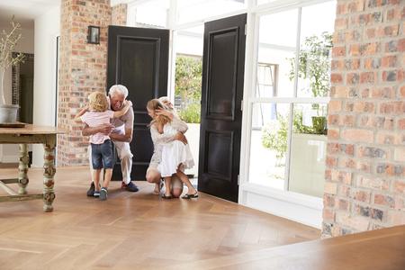 Visiting grandparents bend and kneel to hug grandchildren