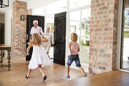 Two excited kids rush to meet their visiting grandparents Standard-Bild