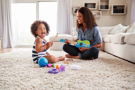 若い黒いお母さんは自宅で幼児の娘とウクレレを果たしています 写真素材