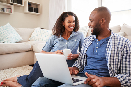 Young black couple using laptop at home look at each other