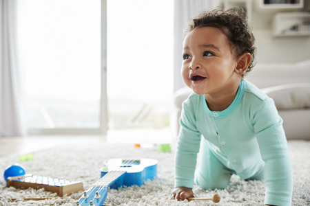 Happy mixed race toddler boy crawling in sitting room Foto de archivo