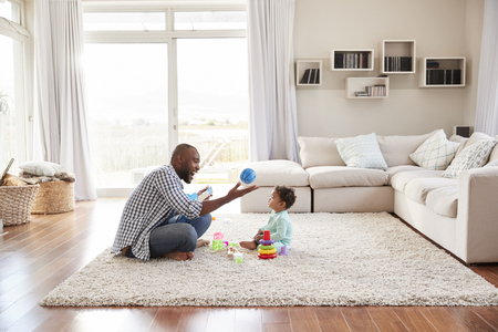 Black father and toddler son playing in sitting room