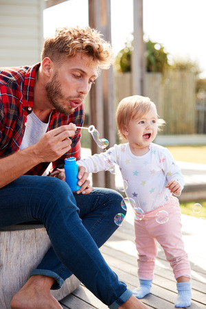Young white father and daughter blowing bubbles outdoors
