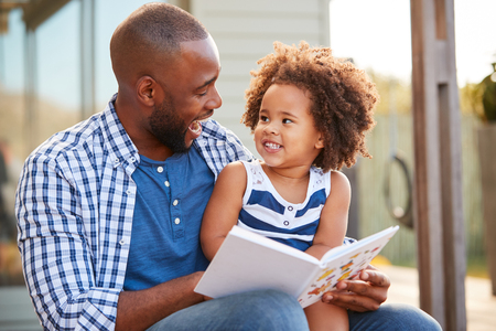 Jong zwart vader en dochterlezingsboek buiten Stockfoto