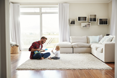 Father playing ukulele with young son in their sitting room Stock Photo