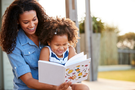 Young black girl reading book sitting on mumÕs knee outdoors Stock Photo
