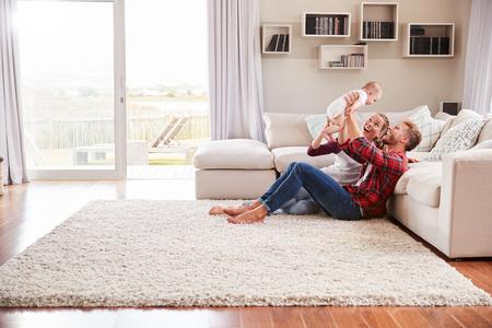 Joven pareja blanca juega con su niño en la sala de estar