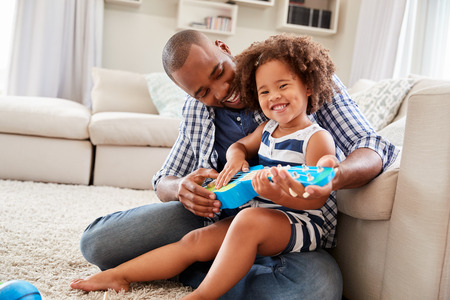 Toddler daughter sits on dad�s knee playing ukulele at home