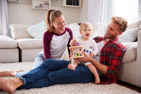Young white family playing together in sitting room Stock Photo