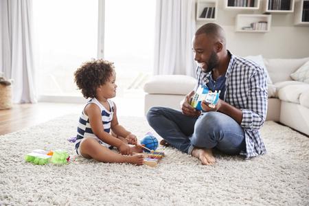 Dad playing ukulele to toddler daughter in sitting room