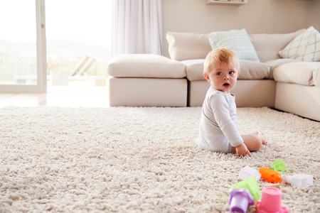 White toddler boy sitting on the floor in sitting room Archivio Fotografico