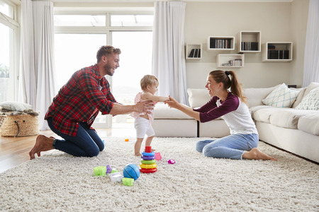 Toddler girl walking from dad to mum in sitting room Stock Photo