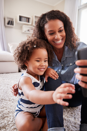 Mother and toddler daughter looking at photos on smartphone