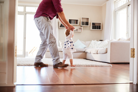 Father helping daughter learn to walk at home, side view Stock Photo