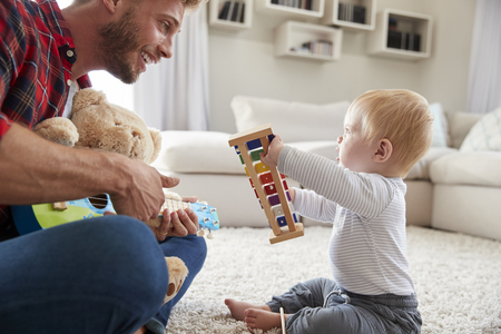 Dad and toddler son play with instruments at home, close up