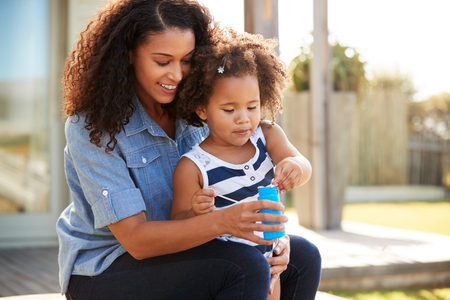 Young mixed race mother and daughter blowing bubbles outside Stock Photo